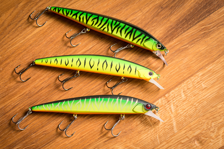 Set wobblers on wooden background. Fishing lures. Фото со стока - 93474396