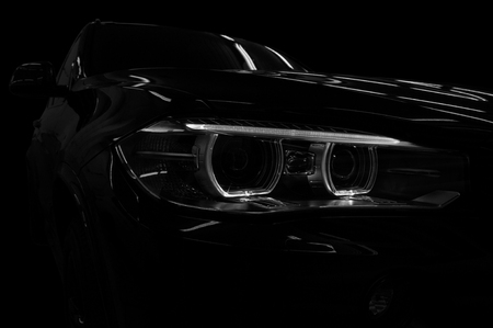 Modern new car on black background. Headlight with backlight. Exterior detail.