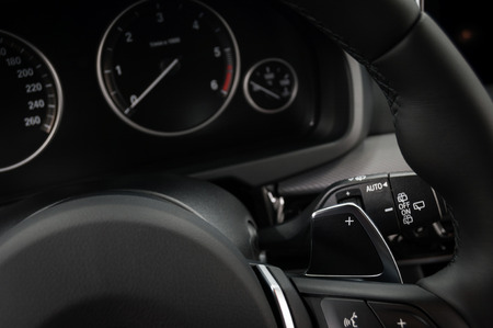 Manual gear changing stick on a car's steering wheel, Modern car interior details. Фото со стока - 94502115