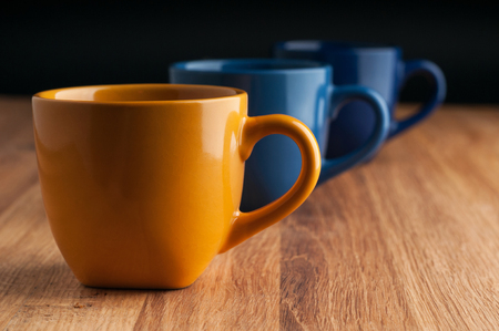 Colorful coffee cups on wooden background. Фото со стока - 95457031