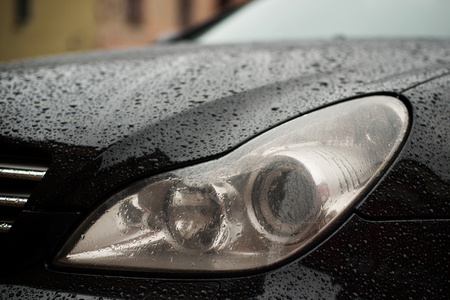 Modern car headlights with rain drops. Transportation background. Фото со стока