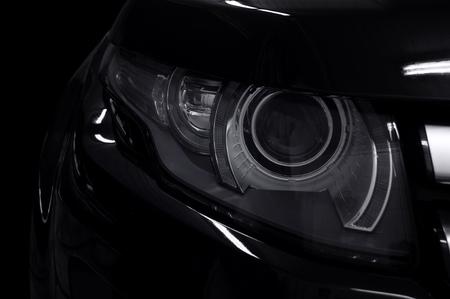 Black car headlights. Exterior detail. Transportation background. Фото со стока