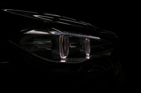 Car headlight on black background. Exterior detail.