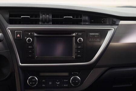 Modern car dashboard with multimedia screen. Interior detail.