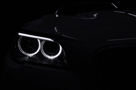 Modern car headlight with backlight on black background. Exterior detail.