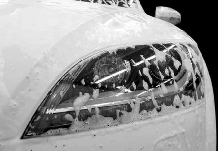 Modern car wash with soap. Auto headlamp covered by foam.