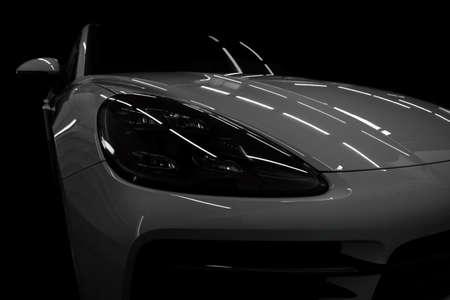 Headlights of new modern car on dark black background. Фото со стока