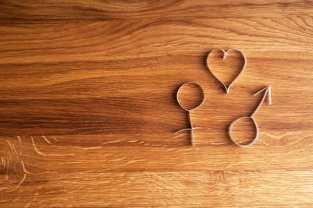 Male and female gender symbols with heart on wooden background. Holiday wallpaper.