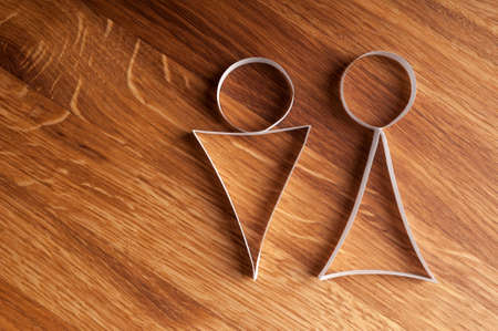 Male and female gender symbols on wooden background. Holiday background.