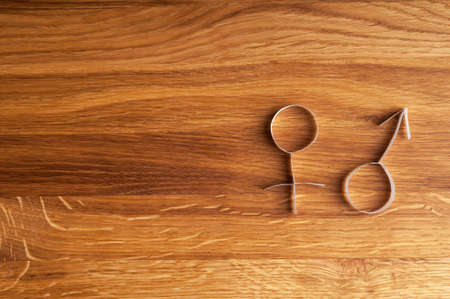 Male and female gender symbols on wooden background with copy space. Holiday background. Фото со стока