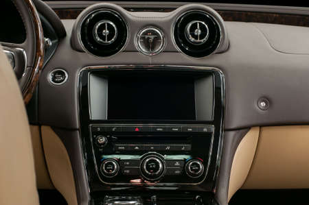 Multimedia screen and control buttons. Luxury car interior.