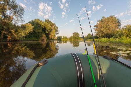Fishing rods on rubber boat. Fishing rural landscape.