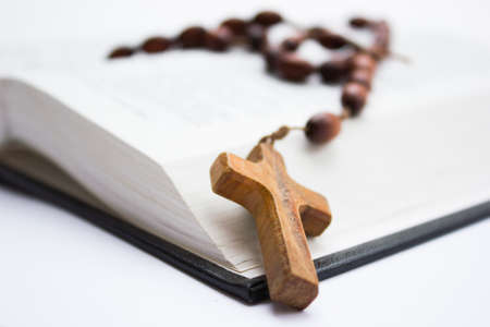 The Holy Bible with a wooden cross on top of it. photo