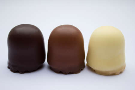 Chocolate covered dark brown, light brown and white marshmallows. photo