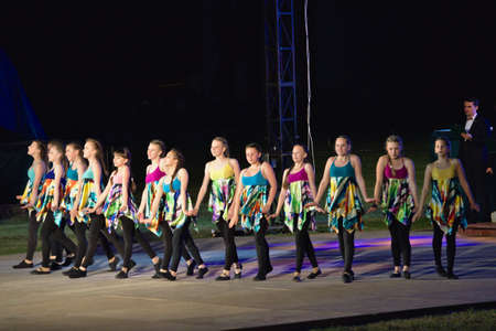 Youth groups perform the song in bright, colorful, shiny outfits at the festive evening.
