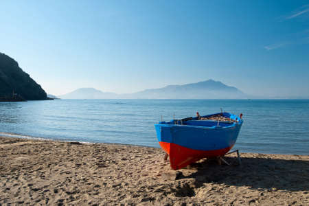 Blue and red boat on the beach, Ischia island on background