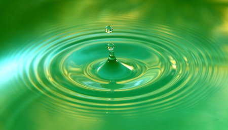 A drop of water is falling. Abstract green background.