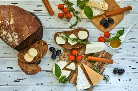 Various cheeses and bread on the table. Fresh dairy products. Cheese selection on a wood table, Gourmet