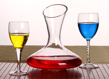 Composition of 3 items, a decanter and glasses with multi-colored liquids. Red, blue and yellow on a white background.