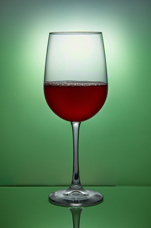 Glass of red wine on green background.