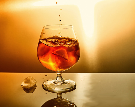Glass of whiskey with drops and ice on an orange background. Glass of whiskey and drops symbol design.