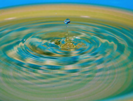 Drop of water or fluid created a ripple wave