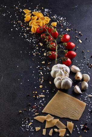 Ingredientes para cocinar pasta sobre un fondo negro. Pasta, tomates jerez, ajo, queso, pimienta y sal.