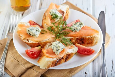 Tasty breakfast. Sandwiches with salmon. and cheese and cherry tomatoes on a wooden white background