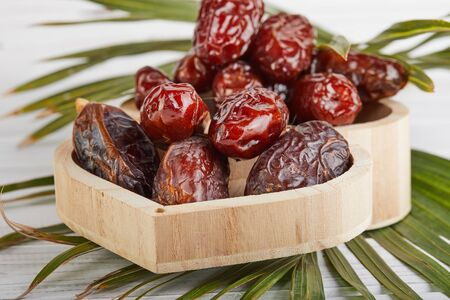 Date fruits with palm leaves, Raw Organic Dates Ready to Eat. Ramadan food and drinks concept Banque d'images