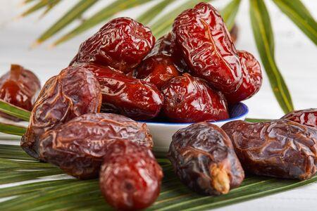 椰枣果实与棕榈叶,生的有机枣即食。斋月食品和饮料的概念