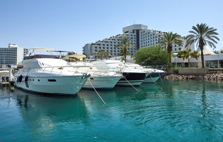 View of the Gulf of Eilat with luxury yachts. On the yacht you can sunbathe, jump into the open sea and enjoy drinks and exotic fruits.