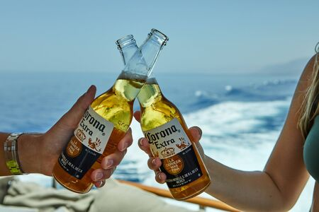Eilat, Israel - July 13, 2019: Male and female hands holding a Corona beer on a luxury yacht on the Red Sea.