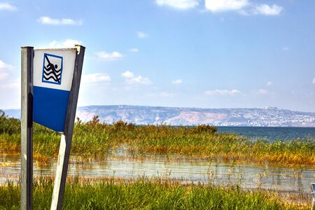 Kinneret Lake coastal strip with bushes and prohibition of swimming