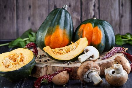 Still life of Green-orange chestnut pumpkins and sliced pumpkin slices with red pepper and mushrooms lying on a dark wooden background