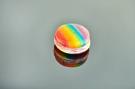 Multi-colored macaron on a gray background with reflection. Stock Photo