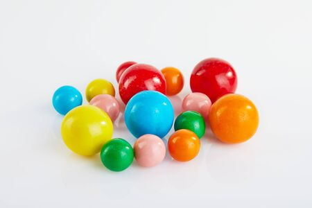 Multi-colored balls of chewing gum on a white background with reflection.
