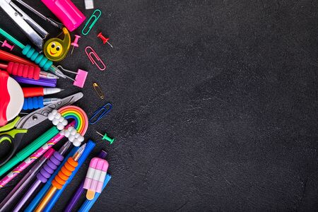 School supplies on black board background with copy space. Back to school concept Stockfoto