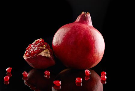 Rosh hashanah - jewish New Year holiday concept. Traditional symbols: pomegranate whole and cut on a black background.