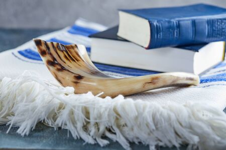 Rosh hashanah - jewish New Year holiday concept. Traditional symbols: Shofar - horn, tallite and Torah on a gray background.
