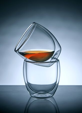 Two glasses for coffee or tea, standing on top of each other with tea in the upper glass with reflection. Stok Fotoğraf