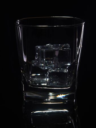 Glass of whiskey with ice on a black background with reflection. Stock Photo