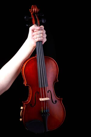 Hand with a violin on a black background, close-up. music concept. Details of the violin.