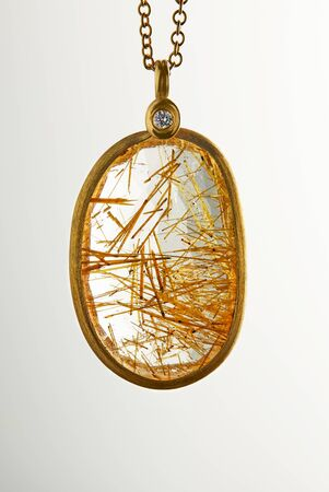 Golden yellow gold pendant with diamond and rutilite stone on a white background. Jewelry production.