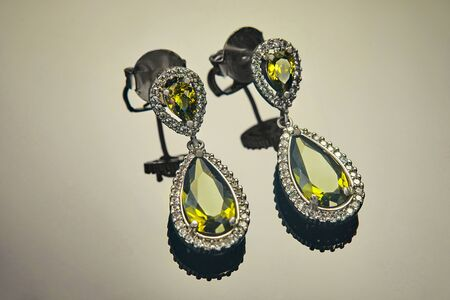 White gold earrings with diamonds and yellow-green stones on a gradient background with reflection. Jewelry production.
