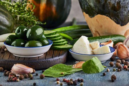 Olive, formaggio, aglio, palline di pepe e cipolle verdi su sfondo blu e un supporto in legno. Mangiare sano concetto.