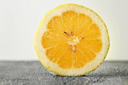 A round slice of lemon backlit on a gray-white background. Stock fotó