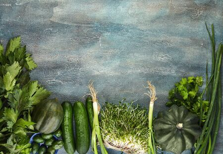 Vegetables and fruits in green colors on a blue background. View from above. Healthy eating concept. Copy space.