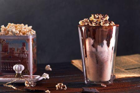 Milkshake with chocolate and popcorn against a dark background. Imagens