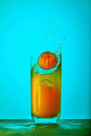 A slice of orange falling in a glass with orange juice and a splash of juice on a blue background. Healthy eating concept.