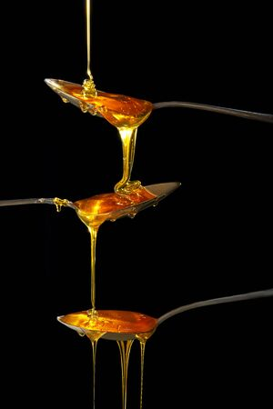 Honey flowing in three spoons from top to bottom on a black background. The concept of movement and healthy eating.